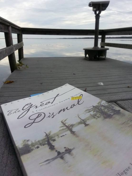 Sitting with a copy of the book by Bland Simpson at the dock at Lake Drummond.