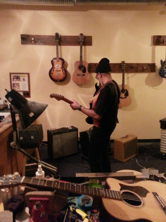 "Lorenzo ""Logie"" Meachum tries out some of Brian's guitars after the Sardine Session at Pinebox studios in Graham."