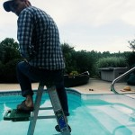 Harvey holds a camera, sitting atop a painter's ladder in the shallow end of a saltwater pool.
